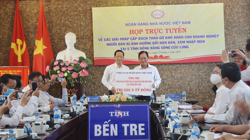 Phó chủ tịch UBND tỉnh Nguyễn Trúc Sơn nhận bảng tượng trưng của Công đoàn Ngân hàng Nhà nước Việt Nam trao hỗ trợ đồng bào tỉnh 3 tỷ đồng khắc phục hạn mặn. Ảnh: C.Trúc