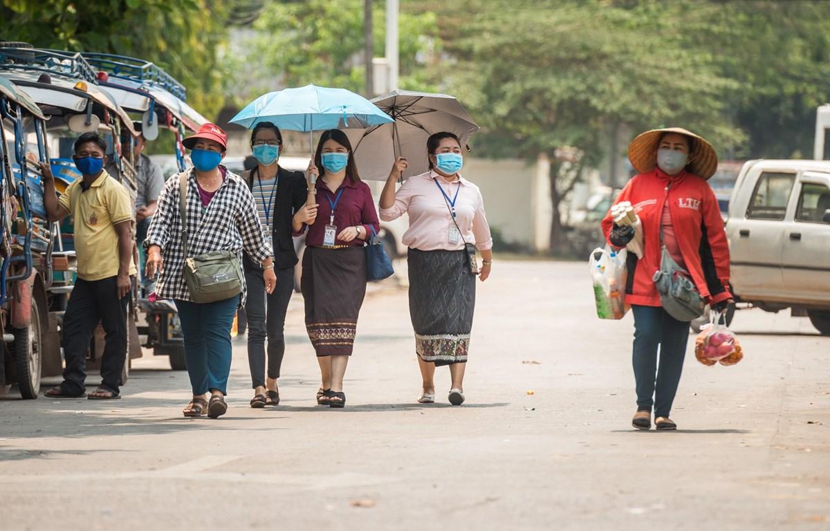 Người dân đeo khẩu trang nhằm ngăn chặn sự lây lan của dịch COVID-19 tại thủ đô Vientiane, Lào ngày 23-3-2020. Ảnh: THX/TTXVN