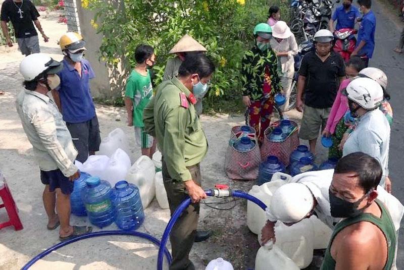 Cán bộ, chiến sĩ cấp nước ngọt cho người dân. Ảnh: Minh Tân