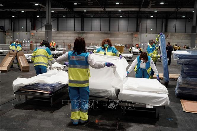 Nhân viên y tế chuẩn bị giường cho bệnh nhân tại bệnh viện dã chiến ở Madrid, Tây Ban Nha, ngày 22-3-2020. Ảnh:THX/TTXVN