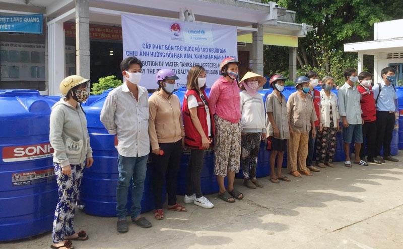 Các hộ dân xã Phú Đức nhận bồn chứa nước ngọt. Ảnh: H. Đức