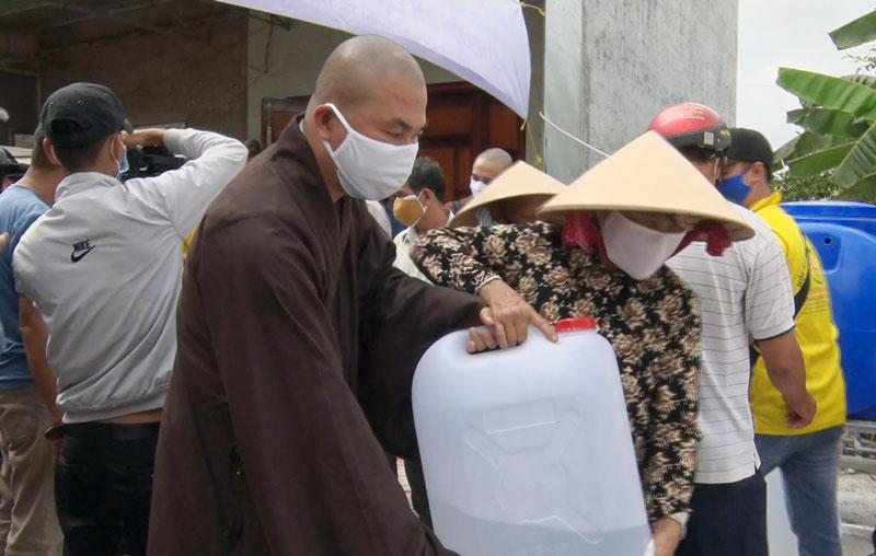 Đơn vị tài trợ tặng can đựng nước cho người dân. Ảnh: Trần Xiện
