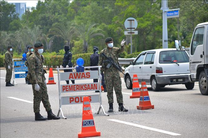 Binh sĩ Malaysia làm nhiệm vụ tại một chốt chặn trong thời gian thực thi lệnh phong tỏa nhằm ngăn dịch COVID-19 lây lan, ở Putrajaya ngày 22-3-2020. Ảnh: THX/TTXVN