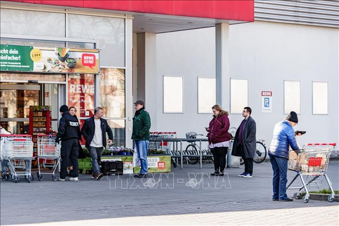 Người dân xếp hàng bên ngoài một siêu thị ở Berlin, Đức ngày 23-2-2020. Ảnh: THX/TTXVN