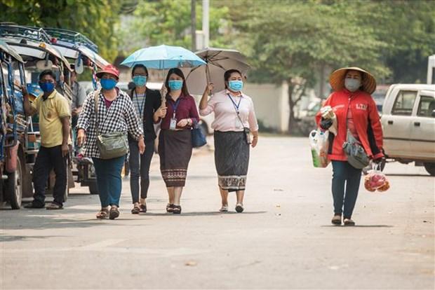 Người dân đeo khẩu trang phòng lây nhiễm COVID-19 tại Vientiane, Lào, ngày 23-3-2020. (Nguồn: THX/TTXVN)