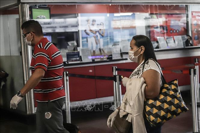 Hành khách đeo khẩu trang để phòng tránh lây nhiễm COVID-19 tại bến xe buýt ở Sao Paulo, Brazil, ngày 22-3-2020. Ảnh: THX/TTXVN