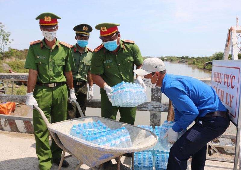 Các lực lượng vận chuyển nước uống vào khu vực cách ly ấp Thừa Lợi, xã Thừa Đức, huyện Bình Đại. Ảnh: Phan Hân