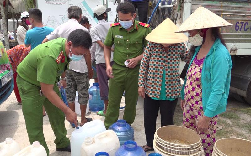 Cán bộ, chiến sĩ Công an tỉnh cung cấp nước ngọt cho người dân ở xã Phước Hiệp, huyện Mỏ Cày Nam.