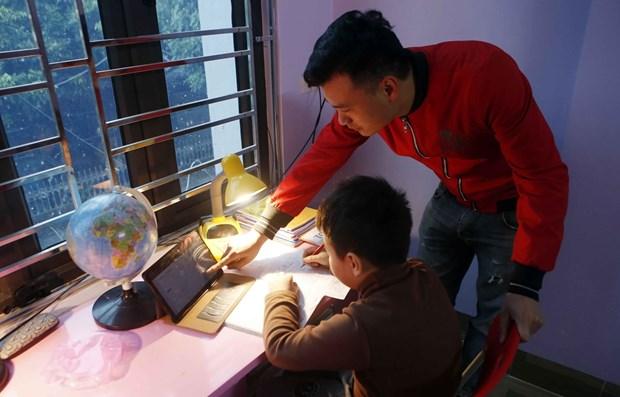 Phụ huynh hỗ trợ học sinh lớp 3 trường Tiểu học Hoàng Lê, thành phố Hưng Yên học trực tuyến tại nhà. Ảnh: Phạm Kiên/TTXVN
