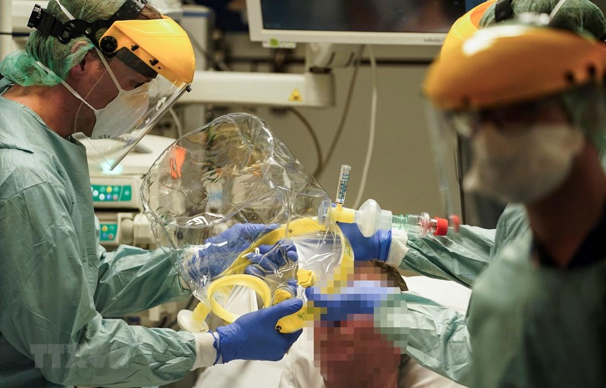 Nhân viên y tế điều trị cho bệnh nhân nhiễm COVID-19 tại bệnh viện ở Brussels, Bỉ, ngày 27-3-2020. (Ảnh: AFP/TTXVN)
