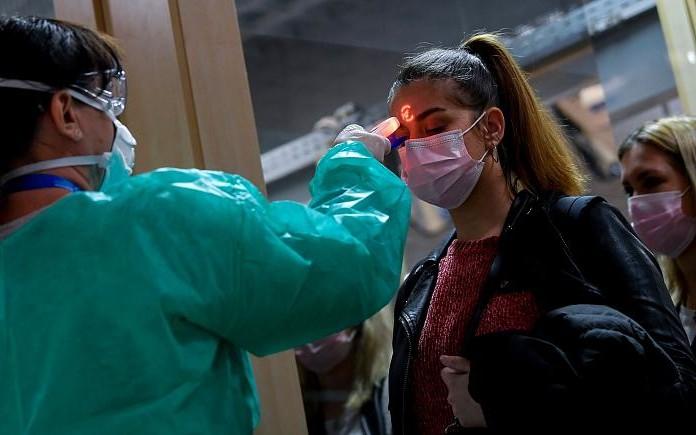 Nhân viên y tế kiểm tra thân nhiệt hành khách tại sân bay. Ảnh: AP