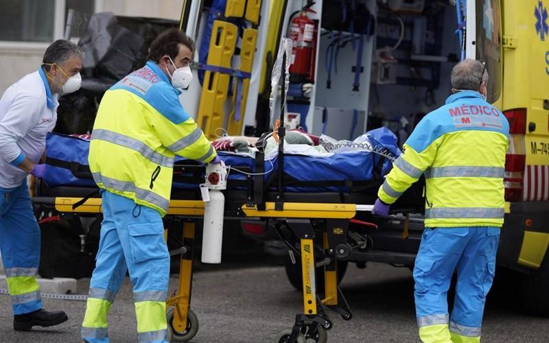 Đưa bệnh nhân đi cấp cứu ở Tây Ban Nha. Ảnh: Bloomberg