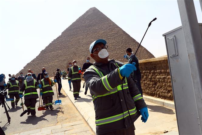 Nhân viên phun thuốc khử trùng để ngăn chặn sự lay lan của COVID-19 tại Cairo, Ai Cập, ngày 25-3-2020. Ảnh: THX/ TTXVN