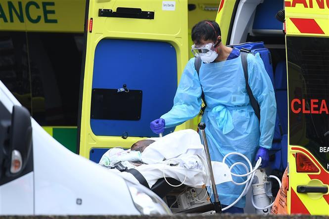 Nhân viên y tế chuyển bệnh nhân mắc COVID-19 từ xe cứu thương vào bệnh viện St Thomas ở London, Anh ngày 31-3-2020. Ảnh: AFP/TTXVN