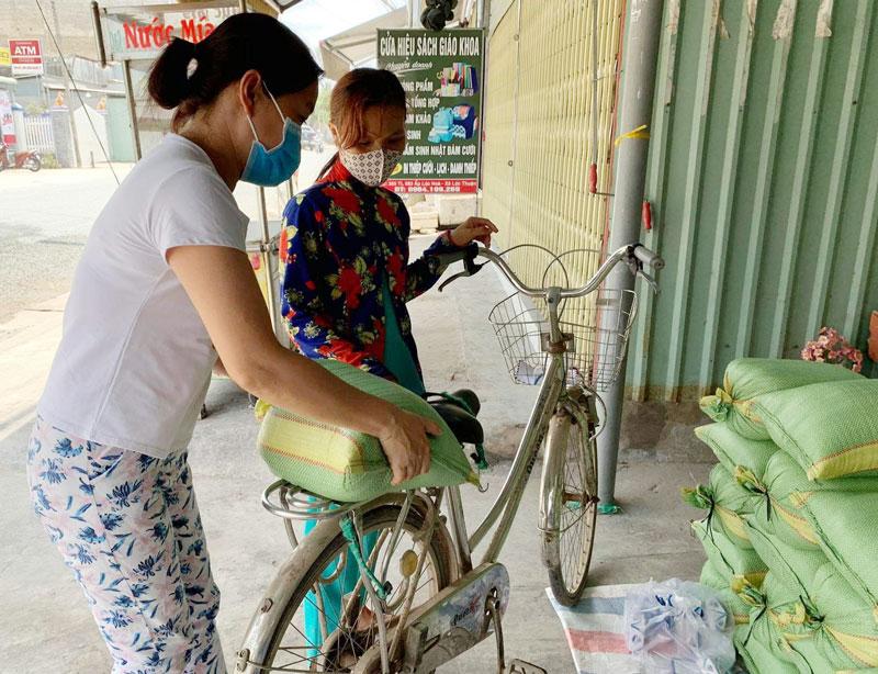 Gia đình chị Mỹ Hạnh tặng gạo cho bà con bán vé số lẻ ở xã Lộc Thuận, huyện Bình Đại. Ảnh: CTV