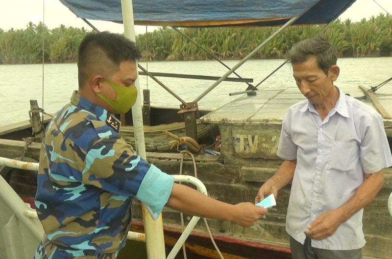 Chỉ huy Tàu 937 phát khẩu trang kháng khuẩn cho nhân dân đến nhận nước ngọt. Ảnh: Công Hoan.
