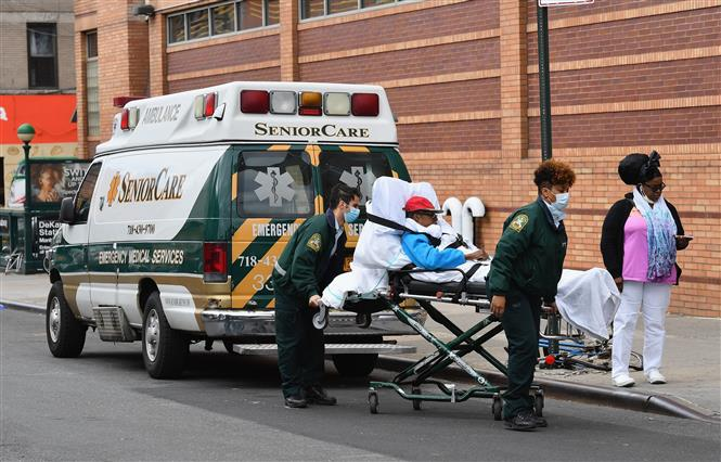 Nhân viên y tế chuyển bệnh nhân nhiễm COVID-19 tới trung tâm y tế ở Brooklyn, New York, Mỹ. Ảnh: AFP- TTXVN