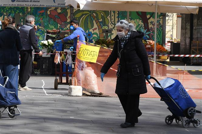 Người dân đeo khẩu trang để phòng tránh lây nhiễm COVID-19 tại Rome, Italy. Ảnh: THX- TTXVN