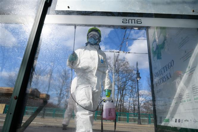 Nhân viên cứu hỏa phun thuốc khử trùng tại trạm xe buýt ở Poznan, Ba Lan nhằm ngăn chặn sự lây lan của COVID-19. Ảnh: AFP- TTXVN