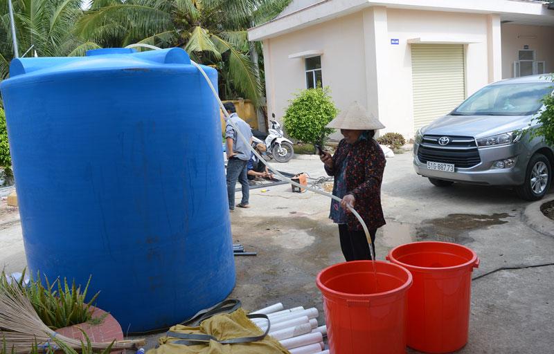 Người dân đến lấy nước ngọt miễn phí tại điểm phát nước xã Châu Bình (Giồng Trôm). Ảnh: A. Nguyệt
