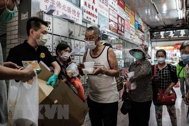 Trong ảnh: Người dân đeo khẩu trang phòng lây nhiễm COVID-19 tại Hong Kong, Trung Quốc. Ảnh: AFP/TTXVN