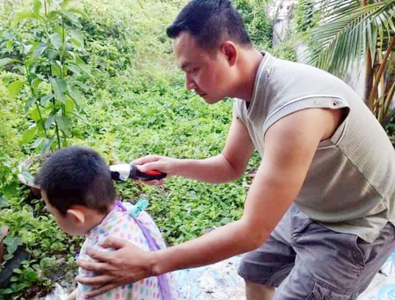 Cha tự tay hớt tóc cho con trai trong thời gian ở nhà tránh dịch bệnh. Ảnh: Thanh Trâm