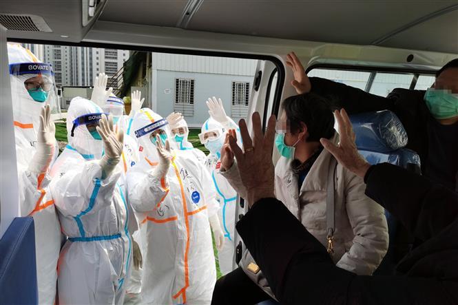 Bệnh nhân nhiễm COVID-19 tạm biệt các bác sĩ sau khi được chữa khỏi tại bệnh viện dã chiến ở Vũ Hán, tỉnh Hồ Bắc, Trung Quốc. Ảnh: THX/TTXVN
