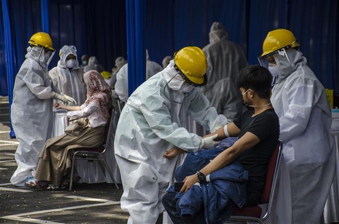 Trong ảnh: Nhân viên y tế xét nghiệm COVID-19 nhanh cho người dân tại Tây Java, Indonesia. Ảnh: THX/TTXVN