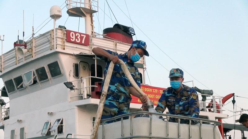 Cán bộ, chiến sĩ Tàu 937 bơm nước lên xe bồn cho nhân dân.
