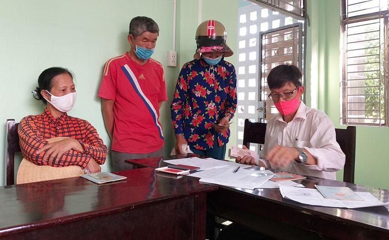 Trao tiền hỗ trợ cho người dân bán vé số lẻ tại UBND xã Hòa Nghĩa, huyện Chợ Lách. Ảnh: Thanh Đồng