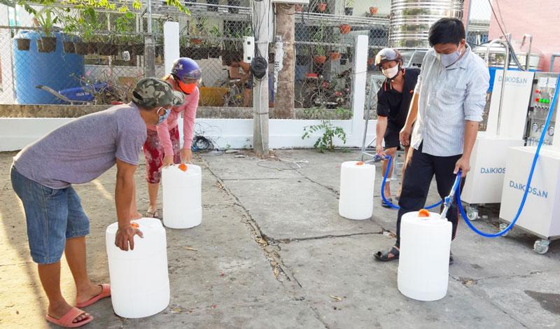 Người dân đến lấy nước tại hệ thống máy lọc nước do ca sĩ Hồ Ngọc Hà tặng. Ảnh Mỹ Xuyên.