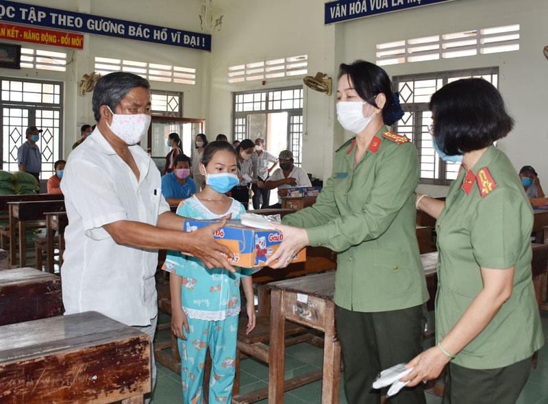 Đại tá Trần Thị Bé Nhân - Phó giám đốc Công an tỉnh tặng quà cho hộ nghèo tại xã An Thạnh. Ảnh: Thảo Giang.