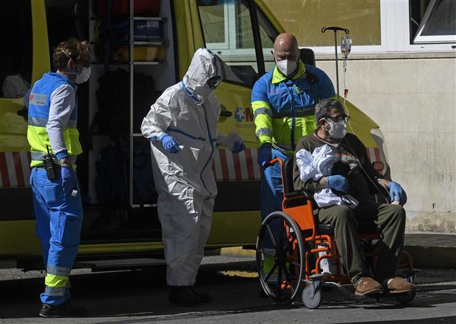 Nhân viên y tế chuyển bệnh nhân nhiễm COVID-19 tới bệnh viện ở Madrid, Tây Ban Nha. Ảnh: AFP/TTXVN