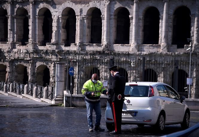 Cảnh sát Italy kiểm tra giấy tờ một lái xe tại Rome, ngày 8-4-2020 khi lệnh phong tỏa toàn quốc được thực thi nhằm ngăn dịch COVID-19. Ảnh: AFP/TTXVN