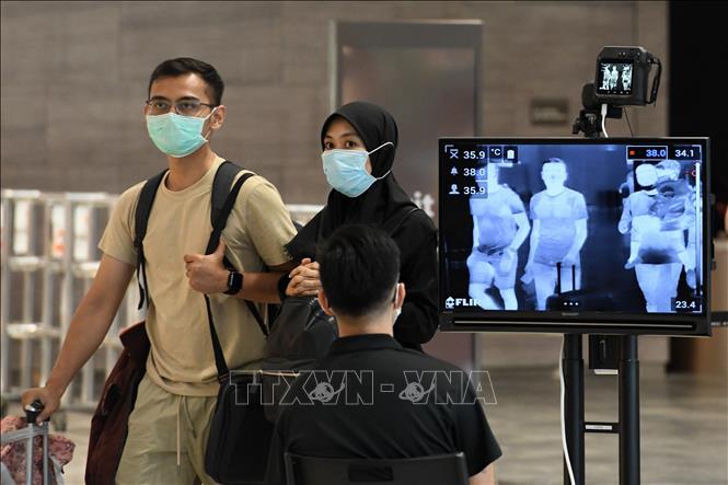 Đo thân nhiệt phòng nhiễm COVID-19 tại sân bay ở Singapore, ngày 27-2-2020. Ảnh: THX/TTXVN