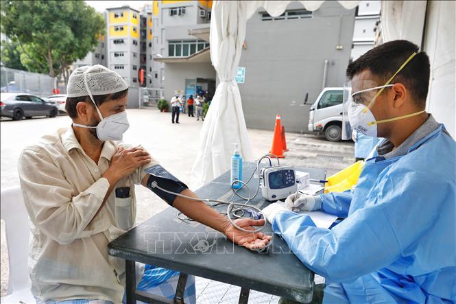 Nhân viên y tế lấy mẫu xét nghiệm COVID-19 tại khu nhà tập thể Toh Guan ở Singapore, ngày 8-4-2020. Ảnh: THX/TTXVN