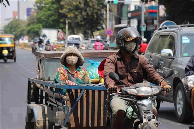 Người dân đeo khẩu trang phòng lây nhiễm COVID-19 trên một đường phố ở Phnom Penh, Campuchia, ngày 25-3-2020. (Nguồn: THX/TTXVN)