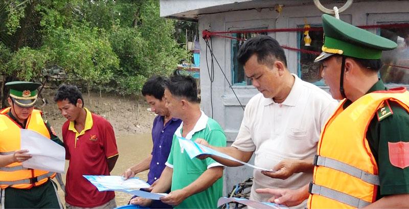 Cán bộ, chiến sĩ Trạm Kiểm soát biên phòng Bình Thắng tuyên truyền cho ngư dân chấp hành nghiêm Nghị định số 42 của Chính phủ. Ảnh: B. Cương
