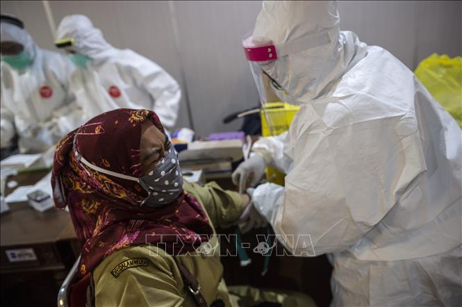 Nhân viên y tế lấy mẫu xét nghiệm COVID-19 tại Surabaya, Indonesia ngày 11-5-2020. Ảnh: AFP/TTXVN
