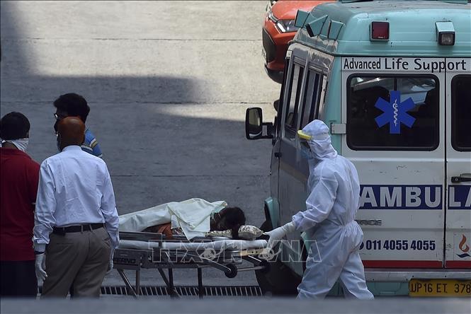 Nhân viên y tế chuyển bệnh nhân nghi mắc COVID-19 từ xe cứu thương vào một bệnh viện ở New Delhi, Ấn Độ ngày 27-4-2020. Ảnh: AFP/TTXVN