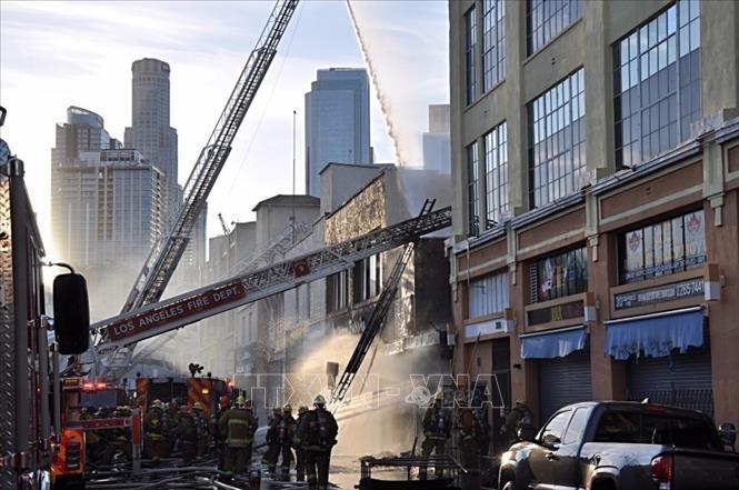 Lực lượng cứu hỏa nỗ lực dập lửa tại hiện trường vụ cháy nổ ở khu trung tâm thương mại Little Tokyo, Los Angeles, Mỹ ngày 16-5-2020. Ảnh: Daily News/ TTXVN