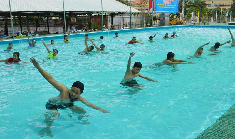 Các em thiếu nhi, học sinh học bơi tại một điểm hồ bơi Mỏ Cày Bắc. Ảnh: A.Nguyệt