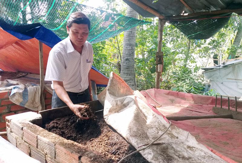 Ông Nguyễn Văn Tròn kiểm tra chất lượng bể ủ phân hữu cơ.