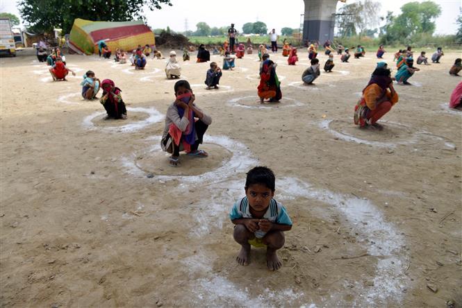 Trẻ em thực hiện giãn cách xã hội phòng lây nhiễm COVID-19 khi xếp hàng chờ nhận bữa ăn miễn phí tại East Delhi, Ấn Độ ngày 11-5-2020. Ảnh: THX/TTXVN