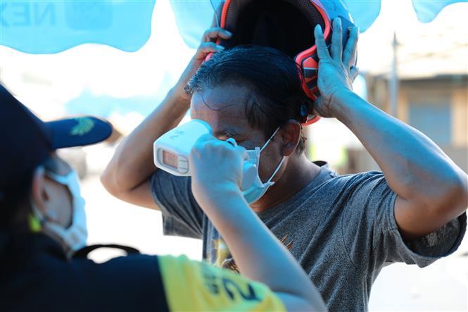 Kiểm tra thân nhiệt của người dân tại lối vào một khu chợ ở Bangkok, Thái Lan ngày 9-5-2020. Ảnh: THX/TTXVN