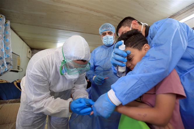 Nhân viên y tế lấy mẫu xét nghiệm COVID-19 cho một em nhỏ tại Baghdad, Iraq ngày 21-5-2020. Ảnh: THX/TTXVN