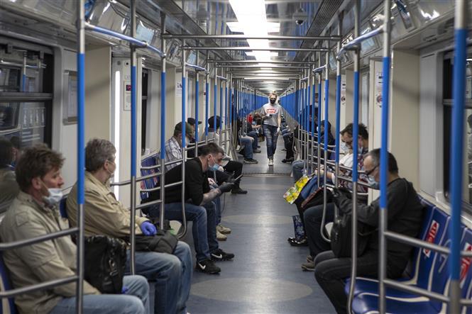 Hành khách đeo khẩu trang và găng tay phòng lây nhiễm COVID-19 trên tàu điện ngầm ở Moskva, Nga ngày 12-5-2020. Ảnh: THX-TTXVN