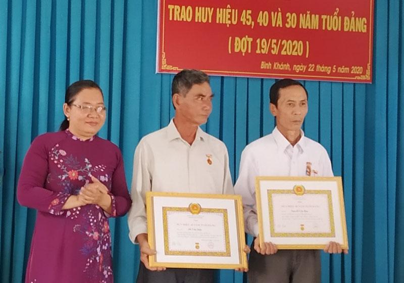 Trưởng Ban Tuyên giáo Huyện ủy Mỏ Cày Nam Nguyễn Thị Trơn trao huy hiệu Đảng cho các đồng chí đảng viên Ảnh: Bảo Toàn