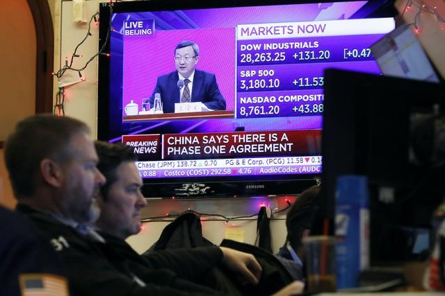 Các nhân viên tại sàn giao dịch chứng khoán New York ngồi trước màn hình chiếu bản tin quan chức Trung Quốc thảo luận về thỏa thuận thương mại với Mỹ. Ảnh: AFP