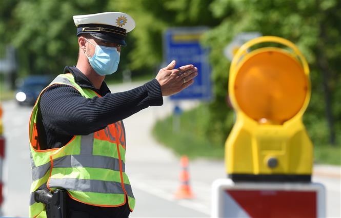 Cảnh sát Đức đeo khẩu trang phòng lây nhiễm COVID-19 khi làm nhiệm vụ tại cửa khẩu biên giới Đức - Áo ngày 7-5-2020. Ảnh: AFP/ TTXVN